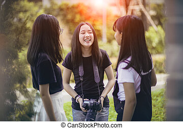 three asian teenager with dslr camera in hand pose as...