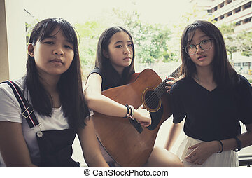 three asian teenager with spanish guitar pose like a music...