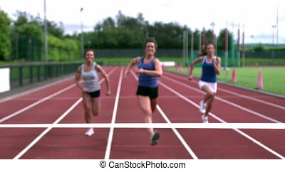 Three athletes running towards the finish line at the track