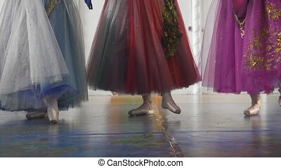 Three attractive ballerinas in colourful dresses dancing on...