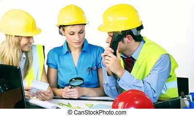 Three attractive engineers working with construction plans