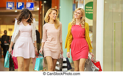 Three attractive girls walking around the shopping mall -...