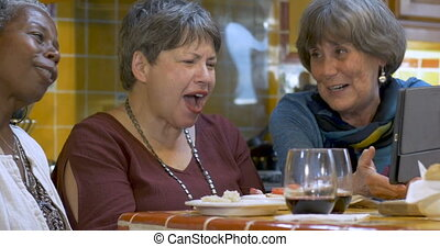Three attractive mature women over 60 viewing a digital tablet together