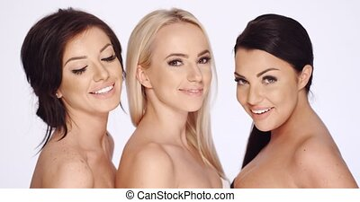 Three attractive sexy women with bare shoulders posing close...