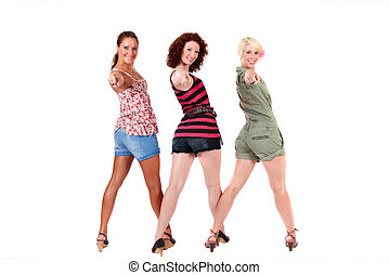 Three attractive young women smiling and pointing at camera. Studio shot. White background