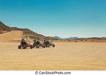 three atv standing in hot desert