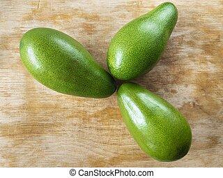 Three avocado lying on a wooden cut board