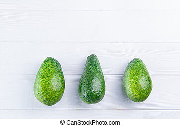 Three avocados in a row. Healthy living, diet, raw eating, vegetable fats concept background. Avocado on the white wooden table. Selective focus, space for text.