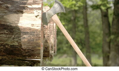 Three axes thrown on a circle log. The axe are flying as...
