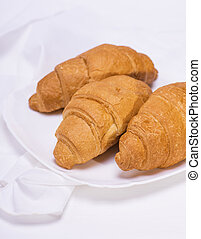 three baked croissants on a white plate