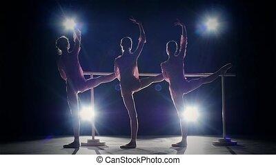 Three ballet girls posing at ballet barre on black. slow motion