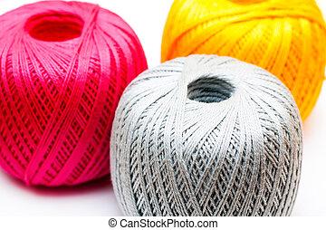 Three balls of yarn on white background.