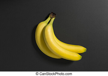 Three bananas on a black background.