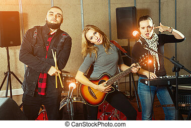 Three bandmates posing together with musical instruments in rehe