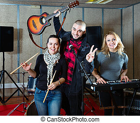 Three bandmates posing together with musical instruments in rehearsal room