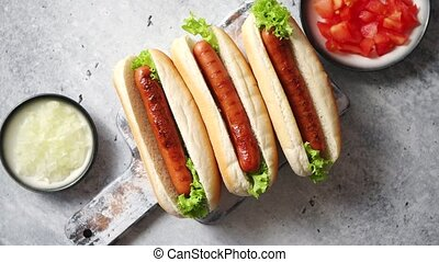 Three barbecue grilled hot dogs with sausage placed on...
