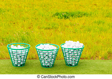 three baskets filled with golf balls on the green grass