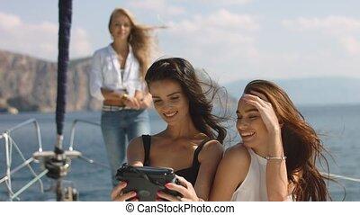 Three beautiful female friends make selfie on a yacht
