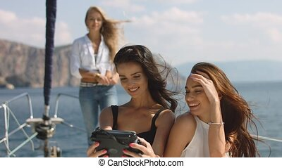 Three beautiful female friends make selfie on a yacht