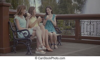 Three beautiful girlfriends eating ice cream on bench