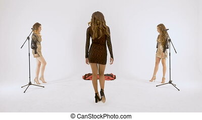 Three beautiful girls are plastic dancing in the studio, on a white background. Video shooting of music video.