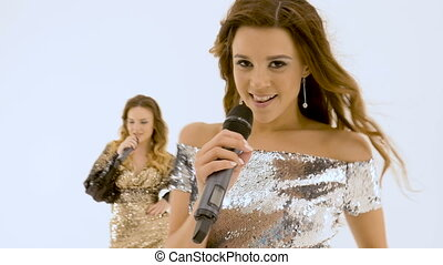Three beautiful girls are singing in the studio. They are on a white isolated background. close-up