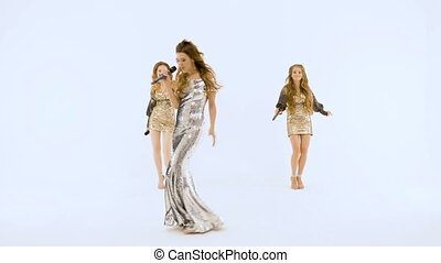 Three beautiful girls are singing in the studio. They are on a white isolated background.