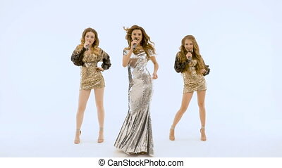 Three beautiful girls in shiny dresses move plasticly and sing. On a white background.