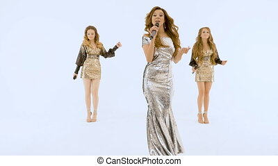 Three beautiful girls in shiny dresses move plasticly and sing.