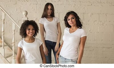 Three beautiful girls in white shirt posing at a photo shoot. Backstage.