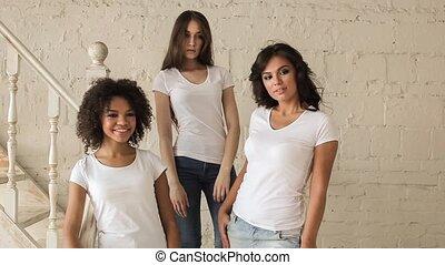 Three beautiful girls in white shirt posing at a photo shoot. Backstage.