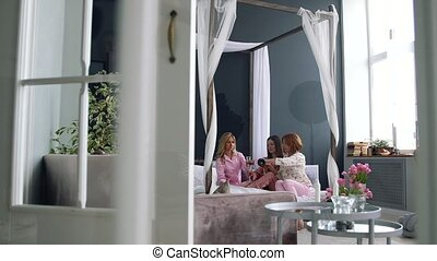 Three beautiful girls sitting on the bed in pajamas banging glasses of champagne talking about the upcoming wedding and talking toast to each other laughing and smiling at each other. To pour champagne from a bottle my friends. To do a selfie at the party.