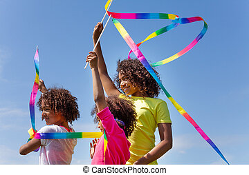 Three beautiful girls waving with color ribbons