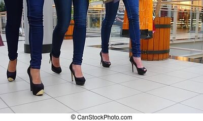 Three beautiful girls with shopping bags goes on shopping center. Slow motion. Legs close up