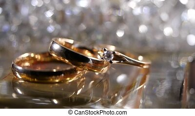 Three beautiful gold rings a diamond engagement ring and an engagement ring lie against a glittering and shimmering background. Gifts and romance, decor, bride and groom, iridescent light and glare