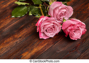 Three beautiful pink roses on wooden table, romantic background