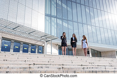 Three beautiful, pretty businesswoman in front of a modern building