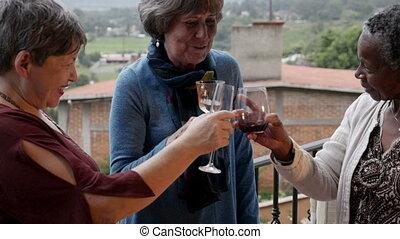 Three beautiful vibrant elderly senior women cheering with wine glasses