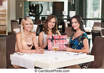 Three beautiful woman sitting at the restaurant. Having birthday present on table