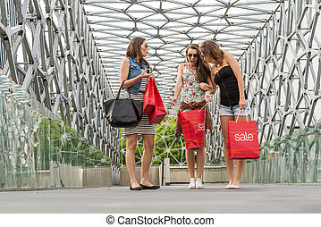 Three beautiful woman walking on the bridge, They Were shopping, shopping bag in his hand