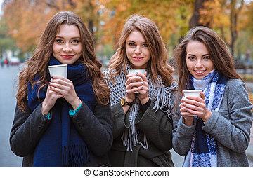 Three beautiful women drinking coffee outdoors