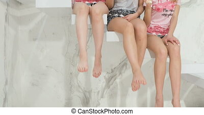 three beautiful young girls sit on the steps and shake their legs. close up