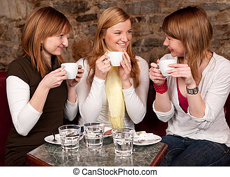 Three beautiful young students waiting drinking coffee and...