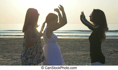 Three beautiful young women dancing on the beach at sunrise