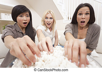 Three beautiful young women friends at home eating popcorn watching a movie together and looking shocked or surprised