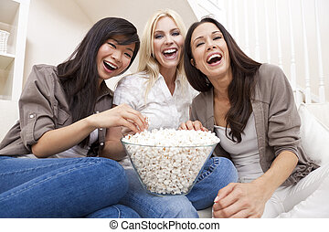 Three beautiful young women friends at home eating popcorn watching a movie together and laughing