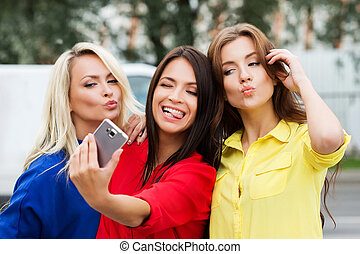Three beautiful young women posing and grimacing while taking a selfie.