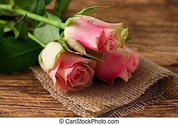 Three beautifull pink roses on jute cloth