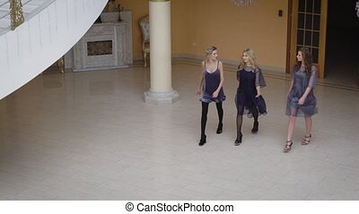 Three beauty strolling through the empty room. One of them wore a sexy dress, two other girls dressed flying dresses of synthetic mesh. Girls confidently go on a long hall