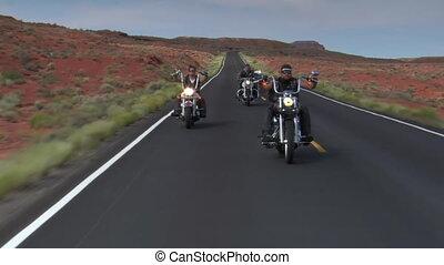 Three bikers on a redrock desert highway